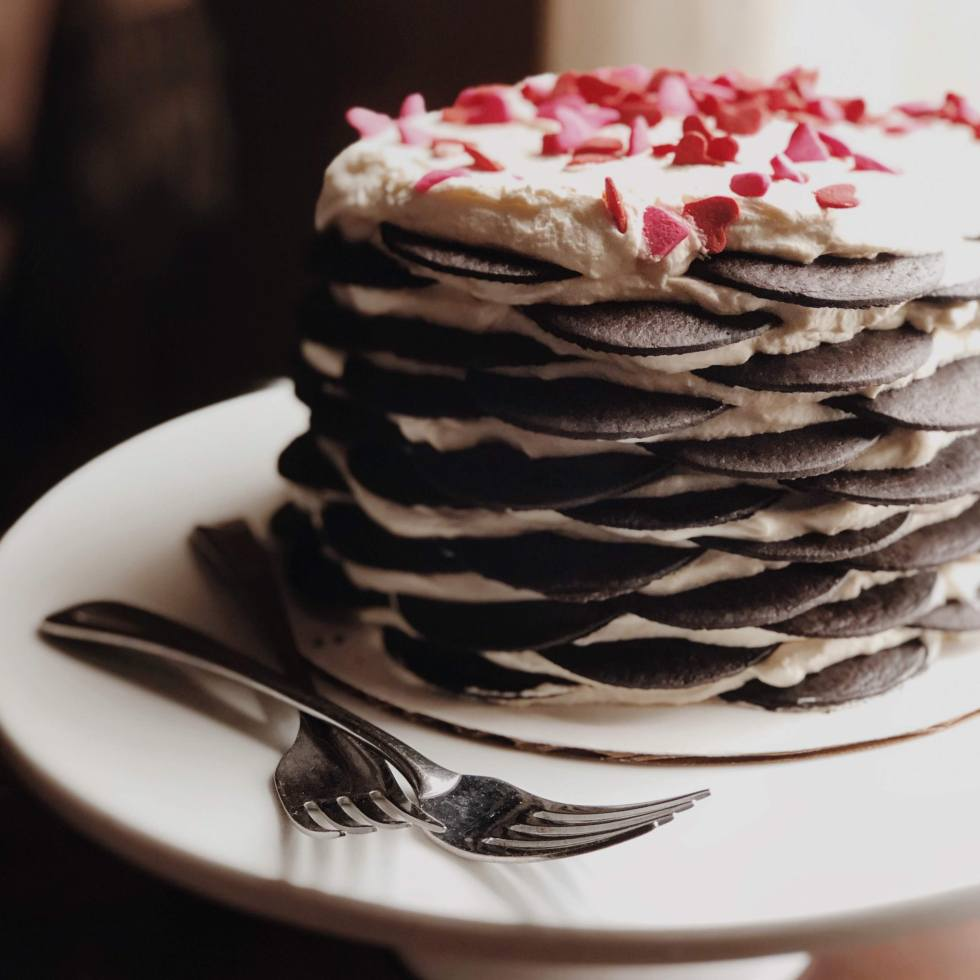 A chocolate icebox cake on a cake stand, made of alternating layers of whipped cream and chocolate wafers
